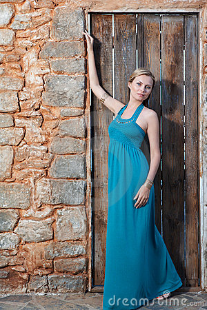 Romantic young blond woman on stone wall back
