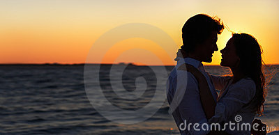Romantic-young couple enjoying a sunset at the bea