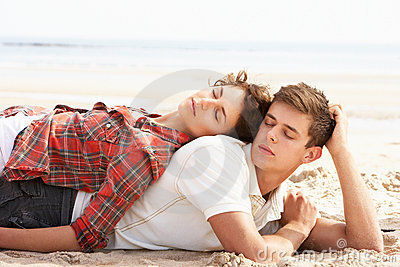 Romantic Young Couple Relaxing On Beach