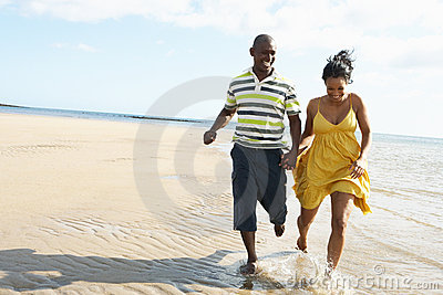 Romantic Young Couple Running Along Shoreline