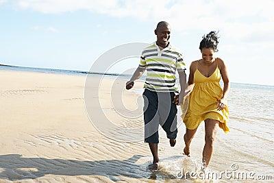 Romantic Young Couple Running Along Shoreline