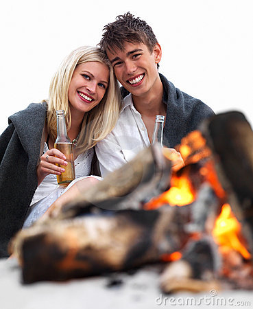 Romantic young couple sitting by bonfire at beach