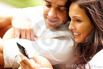 Romantic young couple using a mobile phone