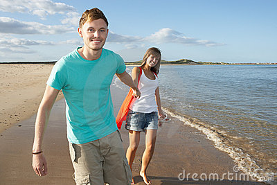 Romantic Young Couple Walking Along Shoreline