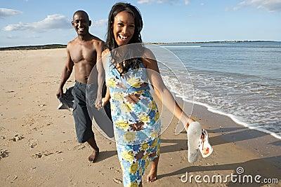 Romantic Young Couple Walking Along Shoreline