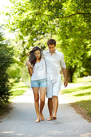 Romantic young couple walking on path in park