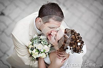 Romantische Kussbraut und -bräutigam an der Hochzeit gehen