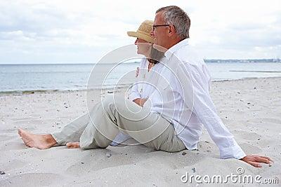 Romantische oude paarzitting samen op strand