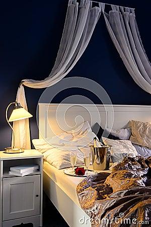 Romantischer Gefühlschampagner des leeren ungemachten Luxusbetts