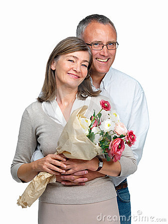 Romatic older couple standing with flowers