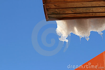 Roof with melting hanging icicles and snow