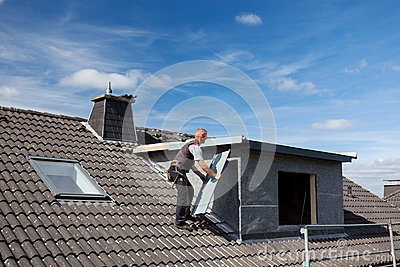 Roofer carrying a metal piece to the dormer