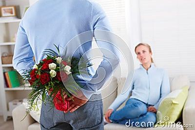 Rosas escondendo do homem romântico atrás de seu para trás