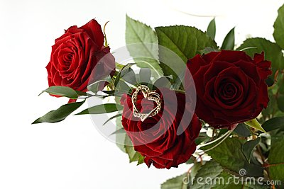 Rose bouquet and gold heart on white background.