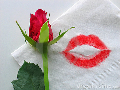Lips a red rose on top of a white folded napkin with a lipstick kiss