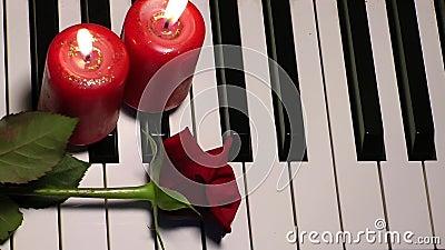Rose y vela en llaves del piano almacen de metraje de vídeo