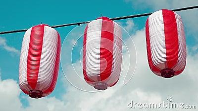 Rot-weiße Laternenleuchten aus Orientalisch Chochin hängen auf weißbewölktem Himmelshintergrund Japanische Signalleuchten stock video