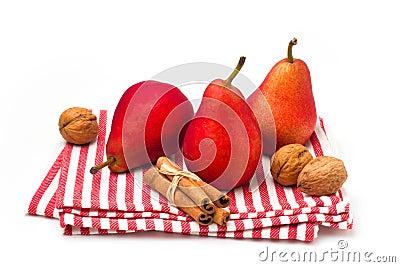 Rote Birnen auf gestreifter Tischdecke