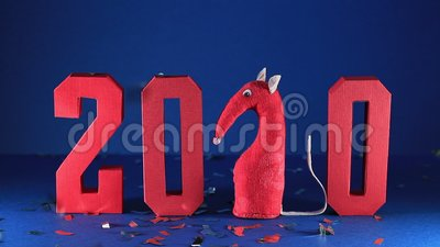 Rote geometrische Zahlen fallen Konfetti vor dunkelblauem Hintergrund Spielzeugratte in Form von Abbildung 2 stock footage