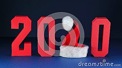 Rote geometrische Zahlen 2020 und fallende Konfetti vor dunkelblauem Hintergrund Weihnachtsmann hat in Form von Abbildung 2 stock video footage