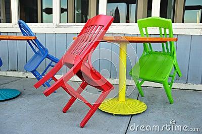 Rote, grüne und blaue Stühle, die auf Tabellen sich lehnen