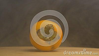 Roterande mogen persimon, som blåser från friskhet och fräckhet på en svart bakgrund, närbilden, ultrarapid, frukter stock video