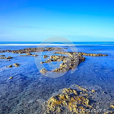 Rotsen in een blauwe oceaan onder duidelijke hemel op zonsopgang.