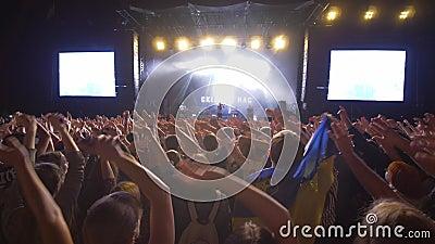 Rotspartij, menigtebewonderaars die handen op levend muziekoverleg golven tegen helder aangestoken stadium met de grote binnen sc stock footage