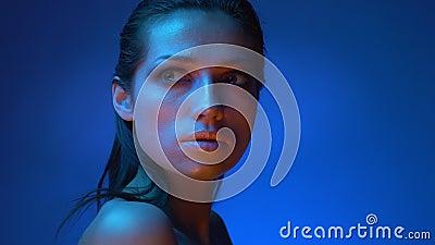 Rougeoyer modèle avec le maquillage brillant se tenant dans les lampes au néon bleues observant au-dessus de l'épaule dans la  banque de vidéos