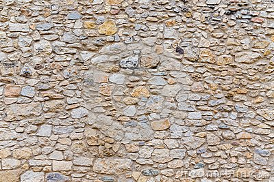 Rough textured old stone block wall
