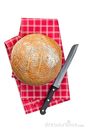 Round bread with knife on checkered napkin