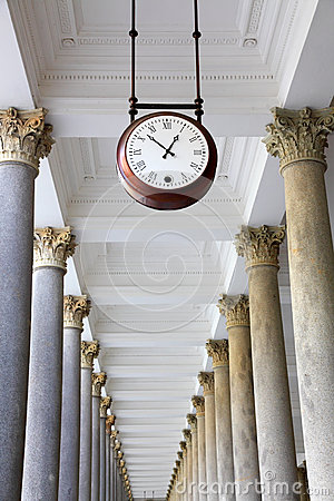 Round clock in a colonnade