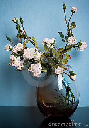 Round glass vase with roses on blue