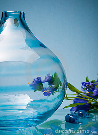 Round glass vase and small flowers on blue