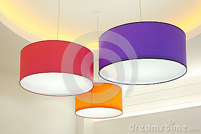 Round stylish lampshades hang from ceiling