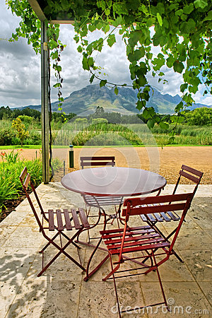 Round Table In Vine covered Outdoor Cafe In Mountains
