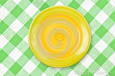Round yellow plate on green checked tablecloth