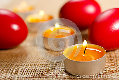 Rounded candles placed between three red egg