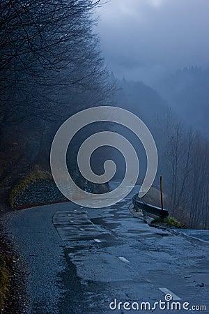 Route humide de montagne au crépuscule