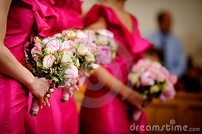 Row of bridesmaids with bouquets at wedding ceremo