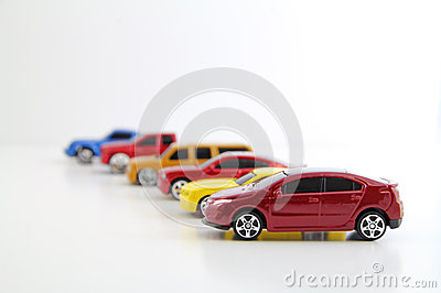 Row of cars with electric car in focus.