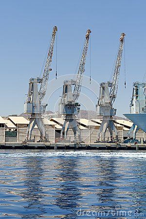 Row of cranes and their reflections in the sea in Eilat harbor