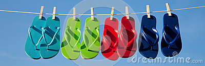Row of flipflops against a blue sky Stock Photo