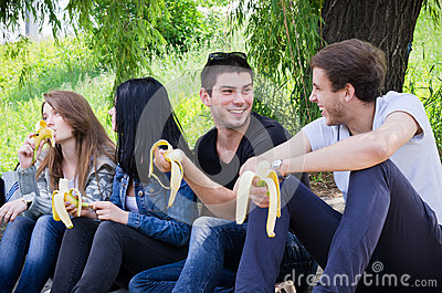 Row of friends sitting together eat banana