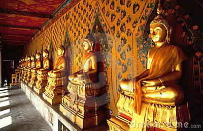 Row of golden Buddhas in Thai temple