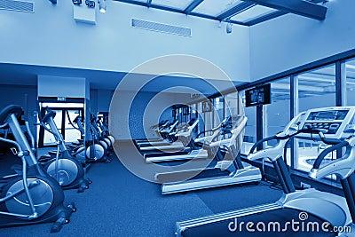 Row of jogging simulators in gym, monochromatic
