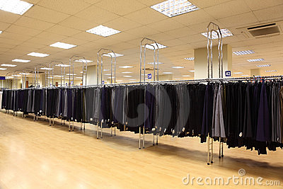 Row men trousers on hangers in shop