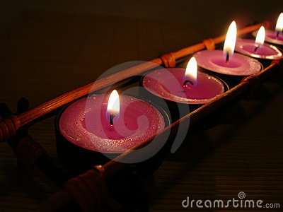 Row of pink candles in darkness