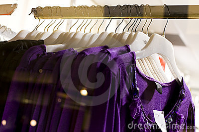 Row of purple blouse garments on display