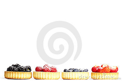 Row of tartlets with sugar covered wild berries